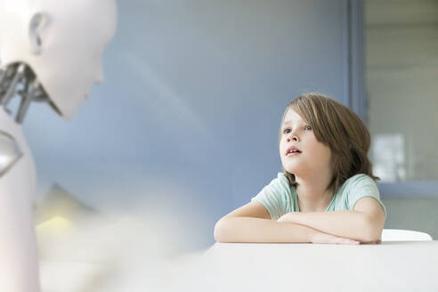 Little boy sitting at table, talking to a robot - KSHSF00013