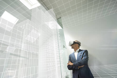 Businessman weraing VR goggles, looking at virtual architcture - KSHSF00016