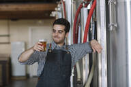 Portrait of confident young man holding beer glass at a brewery - ALBF01075
