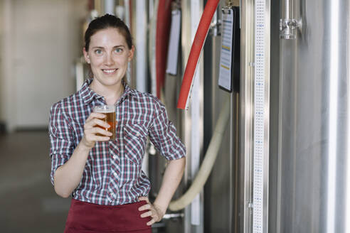 Portrait of confident young woman holding beer glass at a brewery - ALBF01078