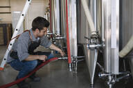Young entrepreneur working at tank at a brewery - ALBF01093