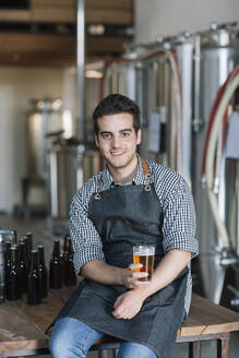 Portrait of smiling young man drinking a beer at a brewery - ALBF01096