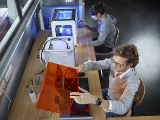 Two technicians sitting at table with 3D printer - CVF01475