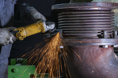 Close-up of worker using angle grinder in a factory - CVF01490