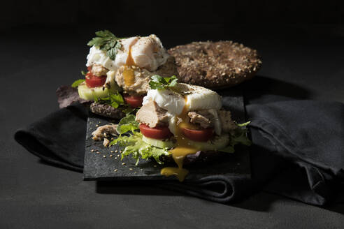 Close-up of open faced sandwich served on table against black background - MAEF12929