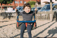 Portrait of happy little girl swinging on a playground - GEMF03118