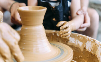 Close-up of father and daughter in a pottery workshop - GEMF03127