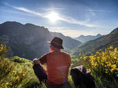 Rear view of senior man sitting on mountain against sky, Alto de La Farrapona, Asturias, Spain - LAF02373