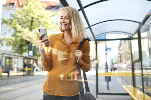 Smiling young woman using smartphone at tram stop - BSZF01336