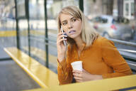 Young woman with smartphone and takeaway coffee waiting for the bus at bus stop - BSZF01339