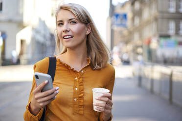 Smiling young woman with smartphone and takeaway coffee in the city - BSZF01342