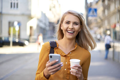 Portrait of happy young woman with smartphone and takeaway coffee in the city - BSZF01345