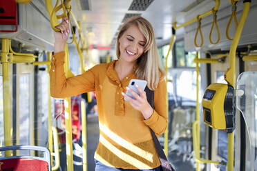 Smiling young woman using smartphone in a tram - BSZF01351
