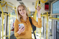 Smiling young woman with smartphone in a tram - BSZF01354
