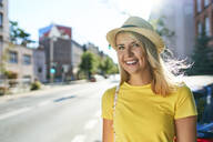Portrait of happy young woman in the city - BSZF01360
