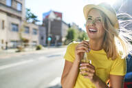 Happy young woman enjoying a drink in the city - BSZF01363