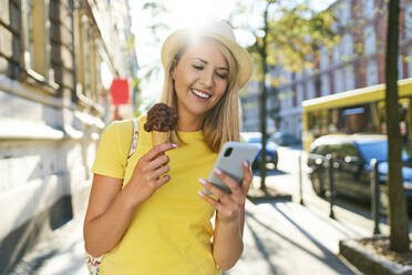 Smiling young woman with ice cream and cell phone in the city - BSZF01366