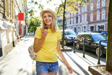 Happy young woman enjoying an ice cream in the city - BSZF01375