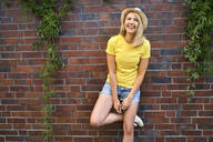Portrait of happy young woman standing at a brick wall - BSZF01378