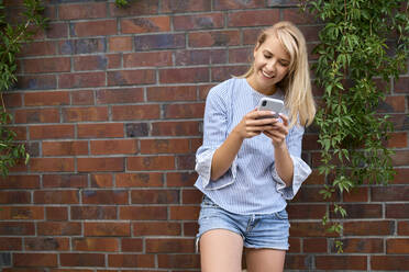 Smiling young woman standing at a brick wall using smartphone - BSZF01384