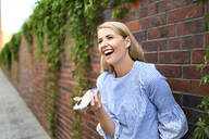 Laughing young woman standing at a brick wall using smartphone - BSZF01387