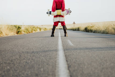 Low section of Santa Claus holding a longboard on country road - JCMF00174
