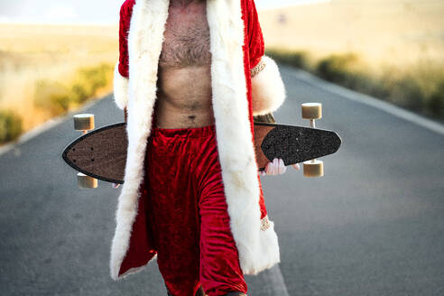Mid section of Santa Claus holding a longboard on country road - JCMF00180