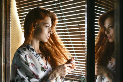 Red-haired tattooed woman at home near the window - JSMF01247