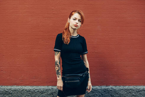 Portrait of red-haired tattooed woman standing at a brick wall - JSMF01262