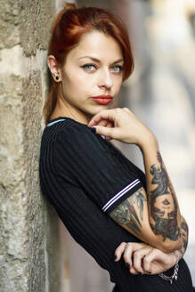 Portrait of red-haired tattooed woman outdoors - JSMF01268