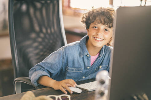 Portrait of smiling boy sitting at desk at home using personal computer - DLTSF00059