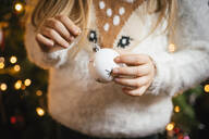 Decorating the christmas tree, girl holding a white bauble with silver stars - IPF00523