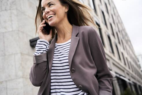 Happy businesswoman on the phone in the city - PNEF01850