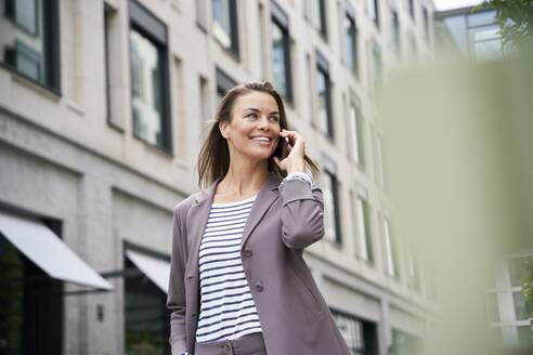 Happy businesswoman on the phone in the city - PNEF01856