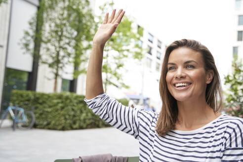 Happy woman hailing a taxi in the city - PNEF01865