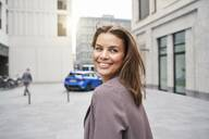Smiling businesswoman with windswept hair in the city turning round - PNEF01868