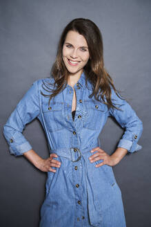 Portrait of smiling attractive woman wearing denim dress - PNEF01961