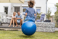 Parents watching son bouncing with hopball in garden - DIGF08144