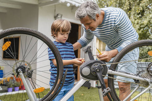 Father and son repairing a bicycle in garden - DIGF08147
