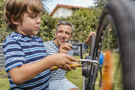 Father and son repairing a bicycle in garden - DIGF08150