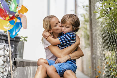 Mother snd son hugging and kissing in garden - DIGF08162