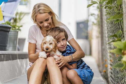Portrait of mother snd son cuddling with cute dog puppy - DIGF08165