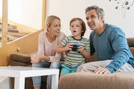 Happy parents with son playing video game on couch at home - DIGF08189
