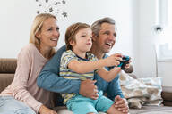 Happy parents with son playing video game on couch at home - DIGF08192
