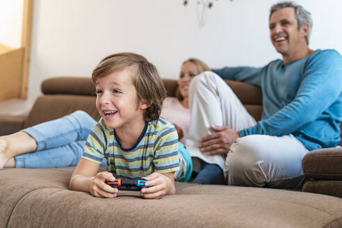 Boy lying on couch at home playing video game with parents watching - DIGF08195