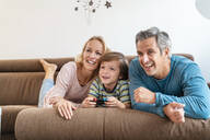 Happy parents with son playing video game on couch at home - DIGF08198