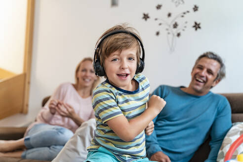 Portrait of boy listening to music with headphones on couch at home with parents in background - DIGF08201