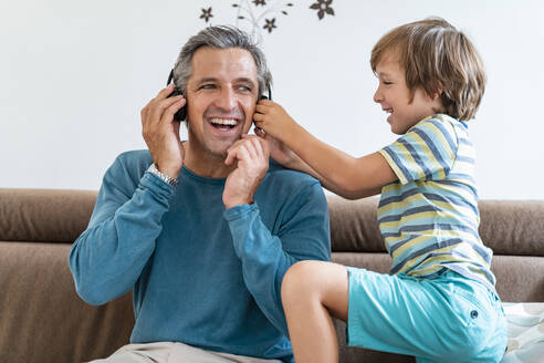 Happy father with boy on couch at home listening to music with headphones - DIGF08204