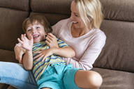 Playful mother and son on couch at home - DIGF08216