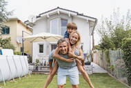 Portrait of father carrying wife and son piggyback in garden - DIGF08225